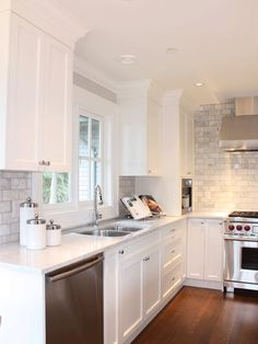 white kitchen cabinets, grey tile back splash, lots of great lighting. Great idea for new kitchen reno.
