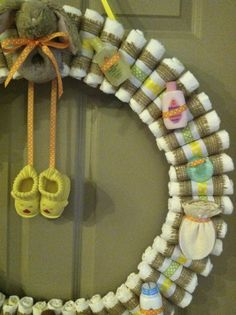 """Diaper wreath (gender neutral & natural themed baby shower) - 24"""" wire wreath frame - roughly 50 size 1 Pampers - each diaper rolled & wrapped in a piece of burlap, then white ribbon w/a rubber band around those -  then wrapped in a thinner green or yellow dotted ribbon & at the same time tied in back to the wire frame - accessories added & tied in back with orange dotted ribbon (travel sized products, organic newborn mittens, wubbanub pacifier, bunny rattle, baby booties, etc)."""