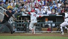 Indiana's Kyle Schwarber tries to declare himself safe while the home umpire rules him out after Louisville catcher Shane Crain tagged him out in the third inning in Saturday's second College World Series game in Omaha. (By Matt Stone, The Courier-Journal) June 15, 2013