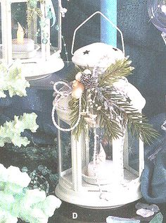 """Snowy white 8"""" lantern with holiday greens, pinecones, seashell trim and a gold-braided cord accent. Uses a votive candle or battery operated tea-light. Bring the beach home for the holidays. $25.. order now for holiday decorating or gifts!"""