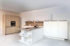 Moderne keuken in T-opstelling. Wit gecombineerd met houtaccenten. Door het open karakter van deze keuken sta je in verbinding met de ruimte op je heen.