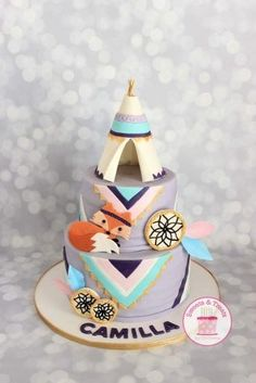 A teepee cake for a first birthday. I used her invitation to make the fox and then the colors came from her decorations. The teepee, fox, and dream catchers are gumpaste and the feathers are colored wafer paper. For the triangles, I cut the design...