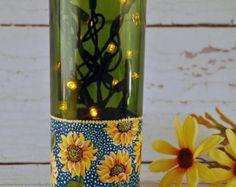Cette bouteille de vin verte clair avec une branche de citron peint serait ajouter une touche décorative unique à votre cuisine.  Une bouteille de vin vide a été récupérée et réutilisée pour créer cette lampe d'accent.  Les étiquettes ont été retirés et la surface de la bouteille a été peint avec une moyenne de glaçage de verre. Un jaune et vert branche de citron a été ensuite peint à la main sur la bouteille.  Un trou a été percé à l'arrière de la bouteille près de la base pour permettre…