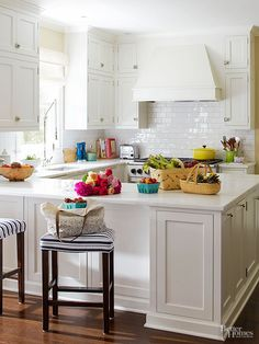 White makes a crisp, clean, and casual statement in the kitchen, but a bit of glimmer from the glossy subway tile backsplash and vintage-inspired hardware takes the style up a notch. An all-white countertop keeps in step with the clean surfaces, while medium-tone wood floors add warmth underfoot. Brooke loves an all-white kitchen because it's clean and bright, the feel she wanted throughout her dream beach house.