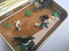 My miniature Koi pond! I made it inside a Altoids tin and made the koi and lily pads using glow in the dark polymer clay. They rocks and plants i used fish aquarium items. Water is clear resin.