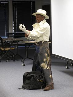 "Charles Sampson puts on his chaps and riding glove as he ""prepares"" for a bull ride. •.♡.• Credit: Kate Miyamoto / USFWS"