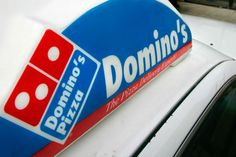 In this Feb. 11, 2007 file photo, a Domino's Pizza delivery sign is shown on a car in Sandy, Utah. - Douglas C. Pizac/AP Photo