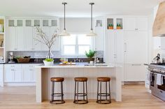 Rustic inspired kitchen with wooden barstools, a white island, and white pendant lights