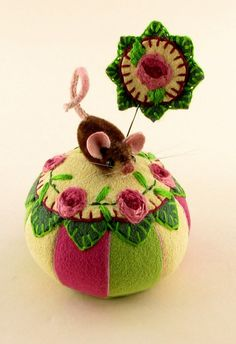"""❤ Rose Garden Mousekin- Hand embroidered roses & leaves surround one of Janie's tiny hand sewn miniature mice topping a gusseted, ultra suede 2 1/2"""" x1 1/2"""" pin cushion hand crafted in spring colors.  With a matching stick pin. Mousekin is hand sewn from vintage dense pile upholstery fabric, & firmly stuffed with wool. His fur has been hand tinted to give him realistic character. The tail & ears are ultra suede; his eyes are black onyx beads.1 1/4"""" nose to rump. ~By Janie Comito…"""