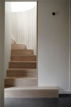 31/44 Architects · No. 49 an elegant minimal rose coloured wooden curved staircase set into white walls