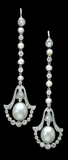 A pair of Belle Epoque natural pearl and diamond drop ear pendants. Each ovoid pearl mounted within a flared millegrained drop set with single-cut diamonds, with a swag of millegrained collet set graduated single-cut diamonds below, the drops each suspended on a chain of alternating seed pearls and millegained collet set single-cut diamonds, to hook fittings, mounted in white precious metal, unmarked.