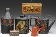 """James D. Julia Images FINE LOT OF SIX DECORATED TOLEWARE PIECES. Lot includes: 1) 5"""" apple decorated teapot. 2) 6"""" h apple decorated tea caddy attributed to Zachariah Stevens with wonderful apple decoration in mustard & red with green highlights 3) 8"""" apple decorated bottle-form tea caddy with a band of red apples. 4) 3-3/4"""" h x 6-3/4"""" w x 3-1/4"""" d hinged trunk box. 5) 1-3/4"""" h miniature trunk. 6) 3"""" miniature coffee pot in red with flower stencil. P)\(1,000-1,500)"""