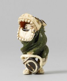 A Tokyo school stained ivory netsuke of a shishi dancer with a drum, by Yasutomo (Hôyû). Late 19th century The dancer is hidden underneath the green mask cloth and pushing up the mask with a movable jaw, the open mouth revealing a child's face inside. Details painted black and brown and inlays of mother-of-pearl. Signed Yasutomo (Hôyû) on an inlaid red lacquer tablet.