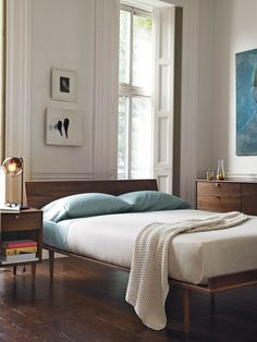 Minimal style wood bed frame with a tasteful cream and light blue color palette