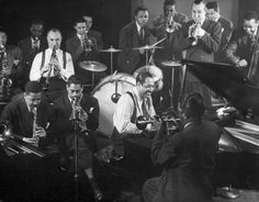 Duke Ellington smiles at the piano as Dizzy Gillespie (seated behind Ellington) and others swing, 1942.