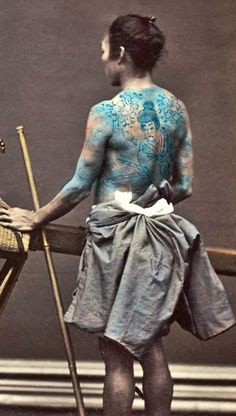 Woman in kago (traveling chair) and two tattooed bearers. 1880's, Japan. Hand-colored photo