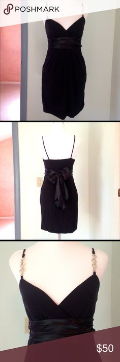 Stunning little black dress Sexy, low cut neckline, beautiful diamond chain accents on the spaghetti straps. Satin sash that ties around the waist in back. You will get many compliments wearing this! Perfect for upcoming holiday parties. Looks brand new. Only wore once to a wedding. Perfect condition. EUC Dresses