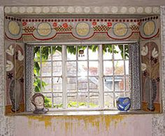 Bedroom at Charleston with decoration surrounding window by Vanessa Bell. The bust on the window sill (left) is by Quentin Bell