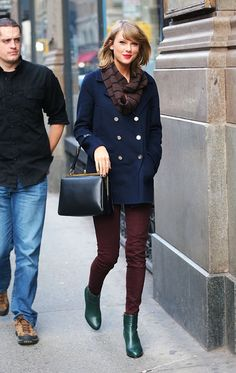 Taylor Swift in a navy peacoat, oxblood jeans, and green booties