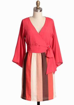 Sakura Breeze Striped Dress By Judith March:  Fall in love with this vibrant coral dress by Judith March featuring ethereal kimono sleeves and glowing with a subtle luminescent sheen. Perfected with a striped skirt in neapolitan hues, a faux wrap waist, and an alluring surplice neckline.