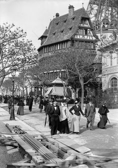''France. 1900 World's Fair, Paris''. From the cut and fit of their clothes these people are probably from the middling ranks of the bourgeoisie. However the woman in the centre is carrying herself with fashionable aplomb. She is holding her skirt train up in the prescribed manner, thereby displaying her figure to advantage.