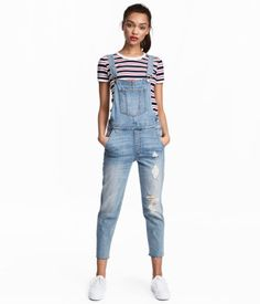 Light denim blue. Ankle-length bib overalls in washed denim with heavily distressed details. Adjustable suspenders, buttons at sides, and mock fly. One