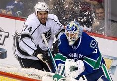 Los Angeles Kings' Dwight King, left, challenges Vancouver Canucks' goalie Cory Schneider