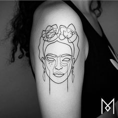 Continuous line Frida Kahlo tattoo on the right upper arm.