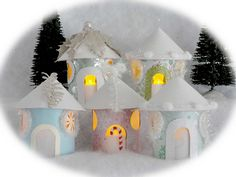 Holiday village made out of cardboard tubes: from gift wrap, paper towel and lint rollers with a flickering LED tealight inside each.