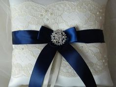 Dark blue ring bearer pillow. This ring bearer pillow is made of ivory satin and navy blue, centered a jewel rhinestone with ribbon to tie your ring.A satin ribbon on the back