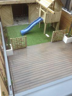 terras van composietplanken, een kunstgrasveld met speeltoestel en een overkapping voor de fietsen