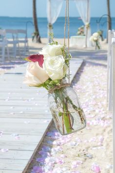 Mason Jar white roses and purple calla, what a simple way to decorate your ceremony chairs perfectly matching wedding arch at Key Largo Lighthouse Beach Wedding Venue in the Florida Keys
