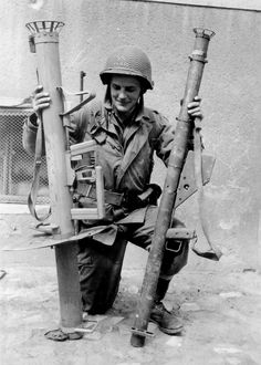 Private Harvey Clark holds a German Panzerchrek (left) and US Bazooka in side-to-side comparison for the benefit of the camera, 1945.