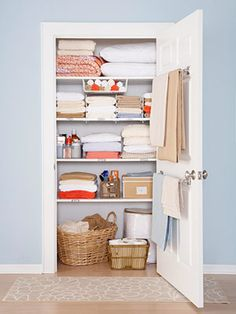 Linen closet organization - laundry baskets (w/ lids) on bottom, sheets, face covers in a basket, blankets up top. Hooks on inside of door to hang massage jacket