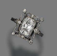 DIAMOND RING, CIRCA 1920 The cushion-shaped diamond weighing approximately 1.75 carats, within a rectangular panel set with small single-cut and rose-cut diamonds, mounted in platinum and white gold