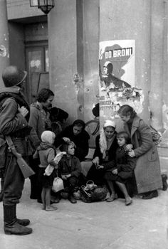 "A Polish family huddle together in front of the Grand Theatre opera house during a German bombing raid, whilst a Polish soldier looks on. The poster in the background reads ""To Arms!"". During the Battle of Warsaw, the Grand Theatre was bombed and...pin by Paolo Marzioli"