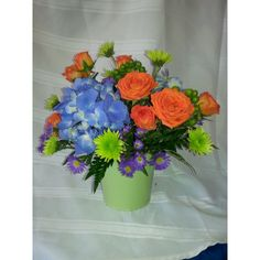 Green tin bucket filled with bright summer flowers.