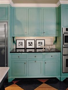 Add these feet to my cabinets. Painting traditional cabinets in turquoise and pairing them with black granite gives this kitchen a contemporary flair.