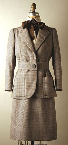 Brown wool tweed suit with ivory silk blouse and brown silk pussycat neck tie, by Norman Norell, American, ca. 1972.