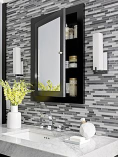 Behind Closed Doors-Recessed into the wall for a clean look, a medicine cabinet keeps creams and cosmetics out of sight, but convenient. The dark accent into the wall of tile breaks up the pattern, providing visual relief.