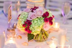 Our wedding centerpieces. Bubble bowl with pink spray roses and green hydrangeas. Looked absolutely beautiful paired with a rustic lantern surrounded by votive candles and shells. Destination wedding in Key West. Flowers by Love in Bloom Florists.