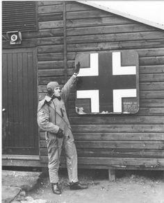 RAF fighter pilot Barry Heath of 661 Squadron delivers a mock Hitler salute next to a fragment of a downed German Dornier Do-215 bomber, 1941.