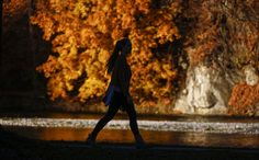 A woman walks along the Isar river past colorful trees during a sunny day in Bad Toelz, Germany, on November 2, 2015.