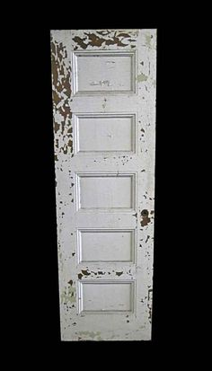 Wooden narrow left swing passage door with five panels and white distressed paint.
