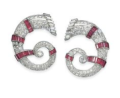 A PAIR OF ART DECO SYNTHETIC RUBY AND DIAMOND CLIP BROOCHES  Each designed as a pavé-set diamond scroll, with baguette-cut diamond terminal and rectangular-cut synthetic ruby line detail, 1930s, 4.0 cm each, with Austrian assay mark for platinum