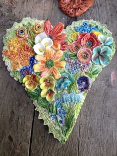 http://katepethoud.blogspot.com/. This is stunningly beautiful! Wow! Ceramic heart with flowers.