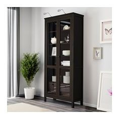 IKEA - HEMNES, Glass-door cabinet, black-brown, , Solid wood has a natural feel.With a glass-door cabinet, you can show off as well as protect your glassware or your favorite collection.The shelves are adjustable so you can customize your storage as needed.1 stationary shelf for high stability.You can hide multiple power strips, etc under the removable bottom shelf.Adjustable feet for stability on uneven floors.The door