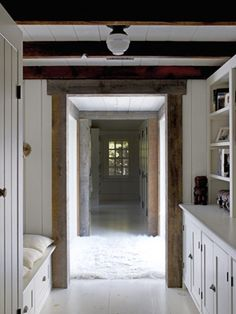 Hallway to a New Addition: a detached barn with studio space on the ground level and a second-floor master bedroom and bath — connected to the main house via a glass-walled walkway that's all but invisible when viewed from a distance.  - Country Living