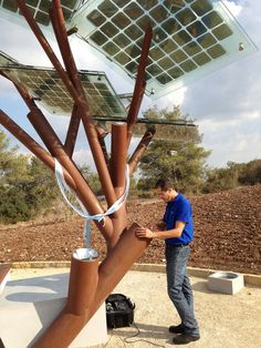 "A man surfs the Internet on a tablet attached to a solar tree in Israel. This tree's broad ""leaves"" are solar panels, powering electric and USB outlets, a drinking fountain and Wi-Fi, all available to people passing by."