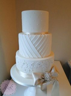 Wedding Cake with pleats, pearls, piped lace and a large bow in ivory, white and champagne